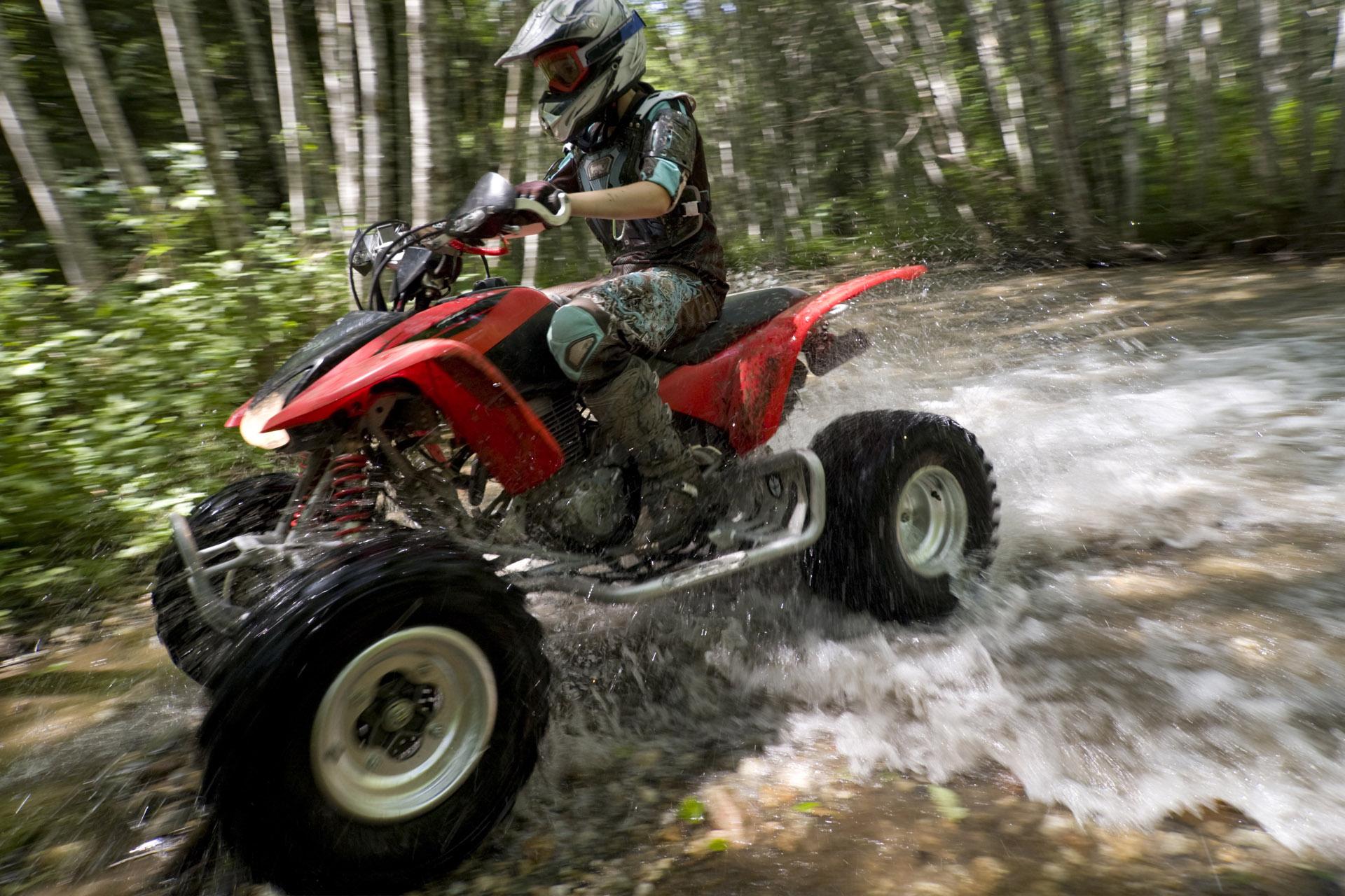 a man riding an ATV crossing the stream